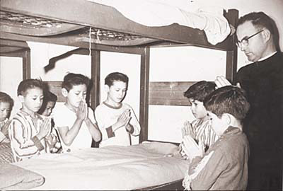 Photo of young American Indian boys, with short-cropped hair, kneeling around a bunk-bed in prayer while an older priest looks on