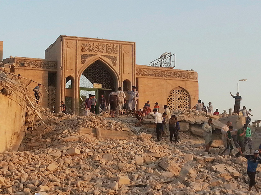 people climbing among the rubble and ruins of the Mosque of the Prophet Yunus (Arabic for Jonah) in Mosul, Iraq