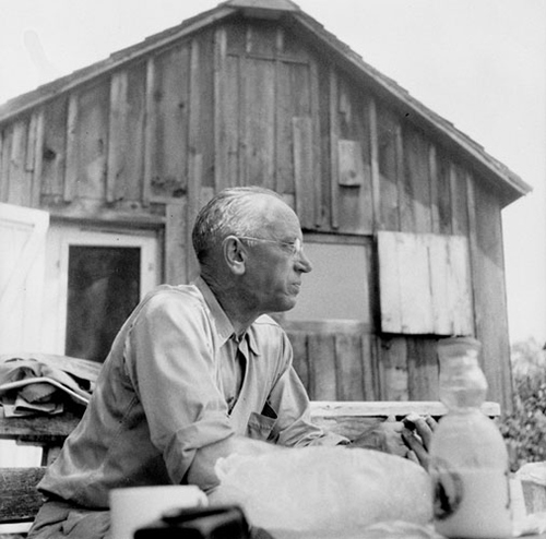 Black and white photo of Aldo Leopold sitting at a bench on his farm in Baraboo, Wisconsin, circa 1940.