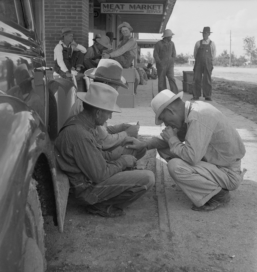 1930s photo of a roadstop in Texas with a group of overall-clad farmers gathered out front