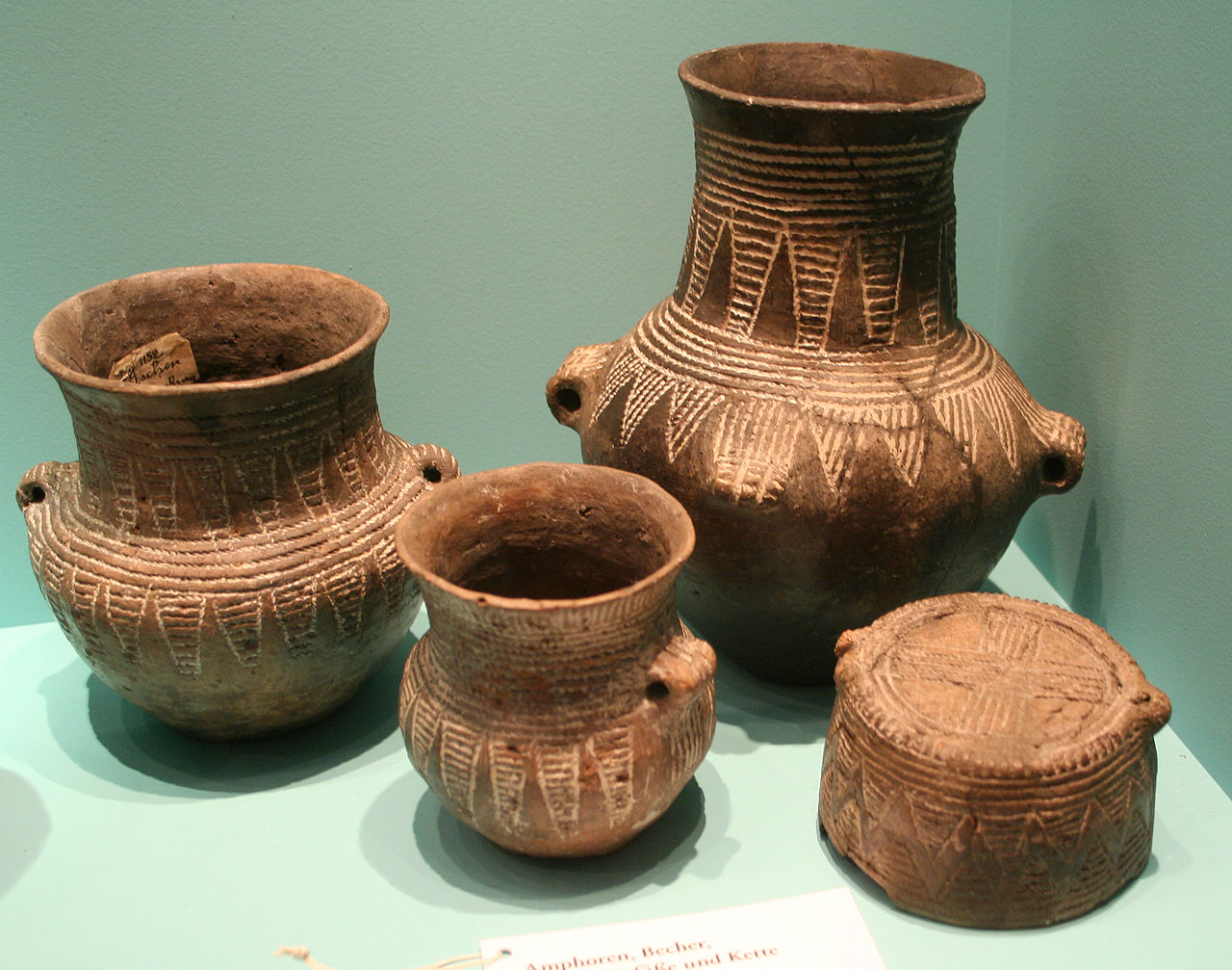 Four ceramic pots, highly decorated with lighter bands created by string during construction.