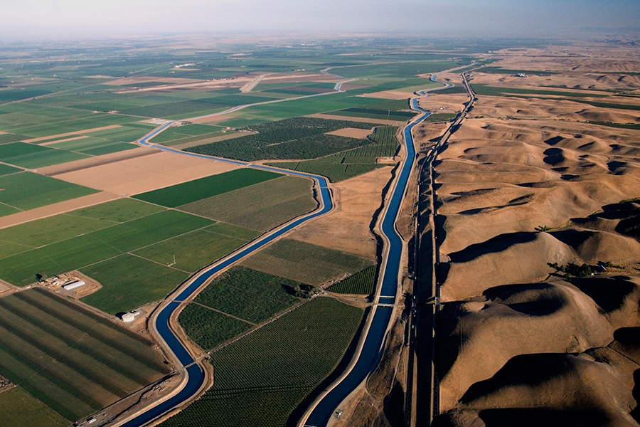 Photo of a water canal running between green agricultural fields on the left, and sand dunes on the right.