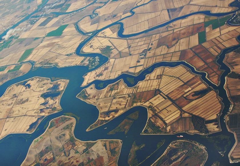 Aerial photo of interconnected rivers and streams that border a patchwork of farms and fields.
